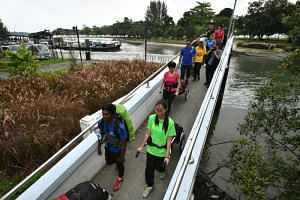Ms Indranee Rajah (in pink) with students pulling their trail walkers across the Changi river footbridge, as part of a camp co-designed by the Ministry of Education and Outward Bound Singapore. The five-day multi-school camp is meant to promote socia