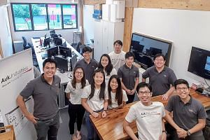 Mr Samuel Tan (left), co-founder and chief executive officer of Auk Industries, which makes industrial productivity tracking systems, posing with his team.