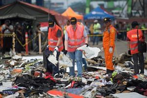 Officials from the US National Transportation Safety Board examine recovered debris from the ill-fated Lion Air flight JT 610 in Jakarta, on Nov 1, 2018.