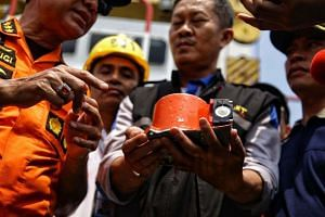 Officials displaying part of the ill-fated Lion Air Flight JT610's black box after it was recovered from the Java Sea.