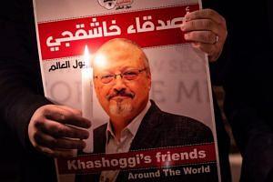 A demonstrator holds a poster picturing Saudi journalist Jamal Khashoggi and a lightened candle during a gathering outside the Saudi Arabia consulate in Istanbul, on Oct 25, 2018.