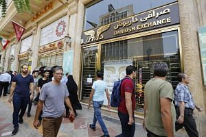 People walk in front of a currency exchange shop in the Iranian capital Teheran.