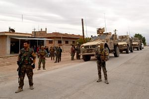 US forces and members of the Syrian Democratic Forces patrol the Kurdish-held town of Al-Darbasiyah in northeastern Syria bordering Turkey, on Nov 4, 2018.