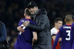 Klopp embraces Liverpool goal scorer James Milner on the pitch after the match.