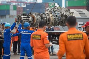Indonesian rescue personnel unloading a recovered engine yesterday from the ill-fated Lion Air Flight JT610 at a port in Jakarta. As of yesterday, a total of 105 body bags had been recovered and handed to police for forensic identification.