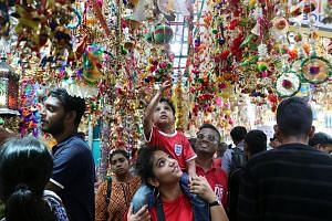 Perched on his mother's shoulders, five-year-old Aaryan Arunan had a better view than most at the Deepavali festival bazaar in Little India yesterday. It was also the perfect spot for the kindergarten pupil to touch the many colourful decorations tha