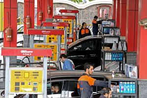 Iranian motorists filling their vehicles' tanks at a petrol station in the capital Teheran yesterday.