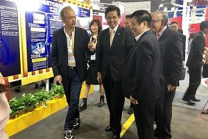 YCH Group executive chairman Robert Yap (left) showing Trade and Industry Minister Chan Chun Sing around his company's booth at the China International Import Expo in Shanghai yesterday.