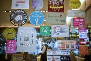 Decals and stickers of various modes of cashless payment at a restaurant in Punggol.