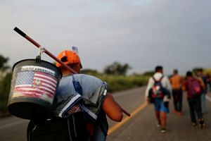 "A migrant from Guatemala, part of a caravan making its way to the US, carrying a bucket with the US flag and text that reads ""American Dream"". The writer says President Donald Trump has effectively defined America as a white ethnic nation that is bei"
