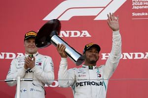 Mercedes' Lewis Hamilton celebrates winning the race on the podium with second placed Mercedes' Valtteri Bottas at the Japanese Grand Prix in Suzuka Circuit, Suzuka, Japan, on Oct 7, 2018.