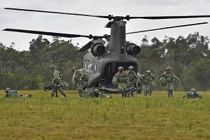 Soldiers fan out and adopt the prone position after deplaning from an RSAF Chinook during a rehearsal for the advance party's landing, part of the helicopter operations in Exercise Trident.
