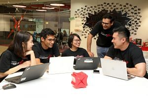 """Impress.AI chief executive officer and co-founder Sudhanshu Ahuja (second from left) with DBS staff, including Mr Bidyut Dumra (second from right), the bank's head of Innovation. Impress.AI worked with DBS to come up with Jim, an acronym for """"Job"""
