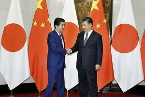 Japanese Prime Minister Shinzo Abe (left) and Chinese President Xi Jinping during a meeting in Beijing on Oct 26. Mr Abe's