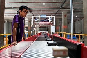 A Qxpress staff monitoring Qoo10 parcels on the conveyor belt to ensure that they are right-side up for scanning. These parcels can now be collected at 7-Eleven stores as well as the nationwide common parcel locker system.