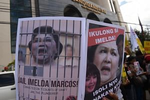 Anti-Marcos demonstrators display placards with portraits of former first lady Imelda Marcos during a protest in front of the anti-graft court in Manila on Nov 13, 2018.