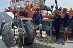 Indonesian navy divers look at the wheels of the ill-fated Lion Air flight JT 610, which were recovered from the sea, north of Karawang on Nov 2, 2018.