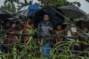Rohingya Muslims behind barbed wire in the Taung Pyo border area where they are stranded between Myanmar and Bangladesh.