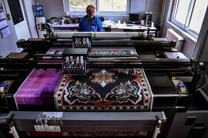 A man works at a silk printing fabric factory in the Greek northern town of Soufli on Oct 10, 2018.