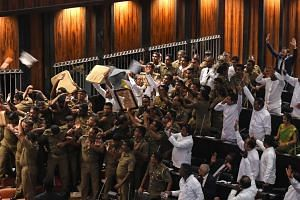 Sri Lankan police escort Parliament speaker Karu Jayasuriya (centre, holding microphone) as aides hold up cushions to protect him and themselves from projectiles thrown by rival legislators in the assembly hall in Colombo on Nov 16, 2018.