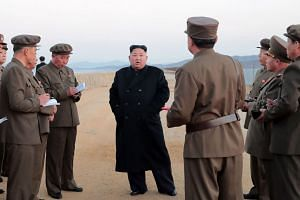 Mr Kim Jong Un standing on a beach surrounded by officials in military uniforms, purportedly at the test site of a new tactical weapon, in an undated picture released by North Korea's official Korean Central News Agency yesterday.