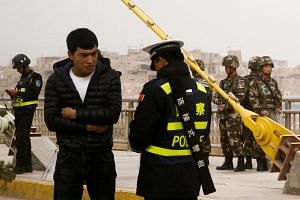 File photo of a police officer checking the identity card of a man in a street in Kashgar, Xinjiang Uighur Autonomous Region, China.