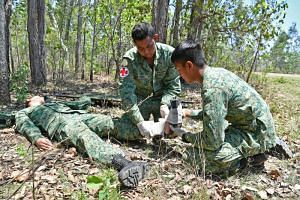 """Singapore Armed Forces (SAF) medics attend to a """"casualty"""" during field training as part of Exercise Wallaby in Rockhampton, Australia. Defence Minister Ng Eng Hen said the higher compensation amounts for injuries or deaths arising from SAF training"""