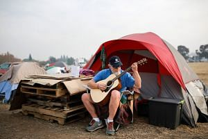 Mr Kelly Boyer plays a guitar he was given outside the tent he has been living in since the Camp Fire destroyed his home in Paradise, in Chico, California.