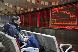 An investor studying an electronic board showing the stock index and prices at a securities brokerage house in Beijing. A government bid to curb risky lending, clean up industry, and restrain home prices is holding firm despite China's slowing growth