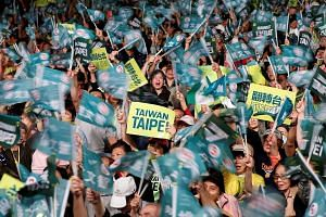 Supporters of the ruling Democratic Progressive Party (DPP) waving to candidates during a campaign rally for the local elections in Taipei on Wednesday. Taiwanese officials say China is seeking to corrode Taiwan's body politic through infiltration an