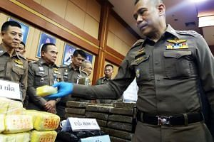 Royal Thai National Police deputy chief Chalermkiat Srivorakhan (right) inspecting seized drugs during a press conference in Bangkok on Nov 23, 2018.