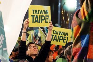 A supporter holds up a sign with English words 'Taiwan, Taipei' at a campaign rally for ruling Democratic Progressive Party's Taipei mayor candidate Yao Wen-chih in Taipei, Taiwan, on Nov 23, 2018.