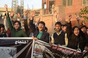Pakistani Shiite Muslims shout slogans during a protest following the blast.