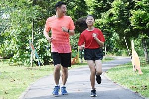 Tan Hui Keong, 42, running with his daughter Michelle, 10, one the youngest participants in this year's Standard Chartered Singapore Marathon. The family goes jogging together two to three times a week.
