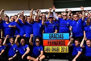 McLaren's Spanish driver Fernando Alonso (blue cap) poses for a photograph with his team ahead of the Abu Dhabi Formula One Grand Prix, his last race for McLaren, at the Yas Marina circuit on Nov 25, 2018.