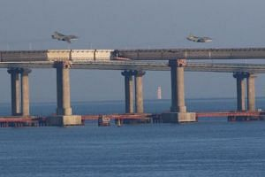 Russian jet fighters fly over a bridge connecting the Russian mainland with the Crimean Peninsula after three Ukrainian navy vessels were stopped by Russia from entering the Sea of Azov via the Kerch Strait in the Black Sea, Crimea, on Nov 25, 2018.