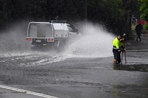 Council workers clear a drain as a car drives through floodwaters on Railway Terrace in Lewisham, Sydney, on Nov 28, 2018.