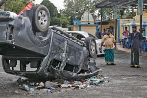A torched car overturned during Monday's violence at Sri Maha Mariamman Temple in Subang Jaya, Selangor. The dispute involving the 147-year-old temple has been brewing for over a decade, with ownership of the land changing hands multiple times betwee