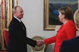 Russian President Vladimir Putin (left) shakes hands with German Chancellor Angela Merkel, during the G20 summit in Buenos Aires, Argentina, on Dec 1, 2018.