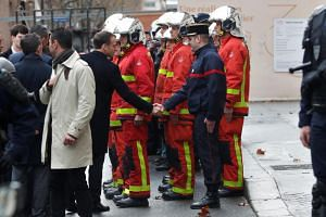 French President Emmanuel Macron shaking hands with a firefighter during a visit in Paris on Dec 2, 2018.