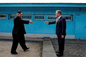 South Korean President Moon Jae-in and North Korean leader Kim Jong Un greeting each other at the truce village of Panmunjom on April 27, 2018.