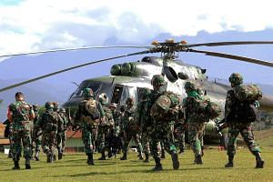 Indonesian soldiers preparing to board a helicopter in Papua province yesterday to retrieve the bodies of the construction workers killed in Nduga district on Sunday. Nineteen employees of state-owned construction firm Istana Karya killed in the inci