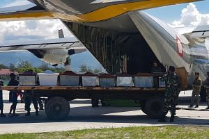 Indonesian military officers load coffins into a carrier aircraft in Wamena, Papua province, on Dec 6, 2018.