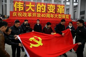 Visitors unfold the flag of the Chinese Communist Party outside an exhibition marking the 40th anniversary of China's reform and opening up at the National Museum of China in Beijing, China, on Nov 14, 2018.