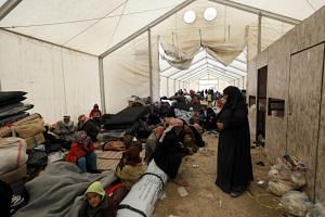 Displaced Syrians from localities of Hajine, Soussa and al-Shaafa gather inside a tent in the Internally Displaced Persons camp on Dec 8, 2018.