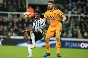 Newcastle United's Ghanaian midfielder Christian Atsu (left) vies with Wolverhampton Wanderers' Irish defender Matt Doherty during the EPL match at St James' Park in Newcastle-upon-Tyne, north east England on Dec 9, 2018.