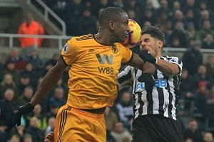 Wolverhampton Wanderers' French defender Willy Boly (left) appears to make contact with Newcastle United's Spanish striker Ayoze Perez in a challenge for the ball during the EPL match at St James' Park in Newcastle-upon-Tyne, north east England on De