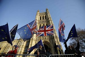 Anti-Brexit activists fly flags showing the colours of the Union Flag and the EU flag outside the Houses of Parliament in London on Dec 11, 2018.