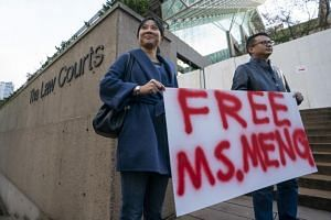Supporters Ada Yu and Wade Meng stand with a sign outside BC Supreme Court before the bail hearing for Huawei Technologies CFO Meng Wanzhou in Vancouver, Canada, on Dec 10, 2018.