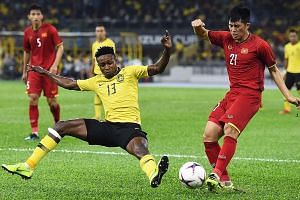 Malaysia's Mohamadou Sumareh (left) attempting to stop Vietnam defender Tran Dinh Trong during the first leg of the Suzuki Cup final yesterday at the Bukit Jalil National Stadium in Kuala Lumpur.